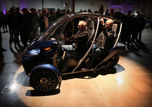 Arcimoto Chief Operating Officer Terry Becker (left) and founder/chairmanMark Frohnmayer debut the newest production model of their electric vehicle before a large crowd at their new west Eugene location.
