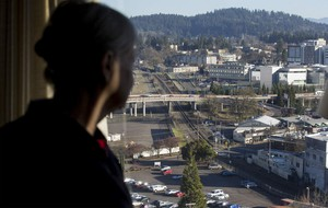 Ya-Po-Ah Terrace resident Judy Crow peers out her 14th-floor window at the train tracks that run through downtown Eugene. Crow is hoping a quiet zone can be enacted to decrease the noise from horns warning of engines approaching crossings.