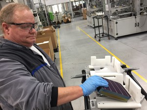 John Clason loads solar cells into a tray to be made into panels at the SolarWorld Americas manufacturing plant in Hillsboro.