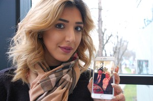 Iraqi refugee Noor Hilmi holds a picture of her parents, who are visiting Dubai. She's been worried they won't be let back in for 90 days.