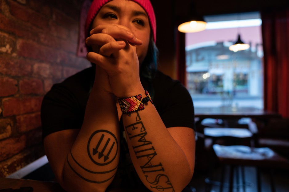 "Rosie Strange sits in a restaurant after the Women's March on Jan. 19, 2019 in The Dalles, Ore. Her left arm says ""FEMINIST"" and her right arm has an anti-fascist symbol on it."
