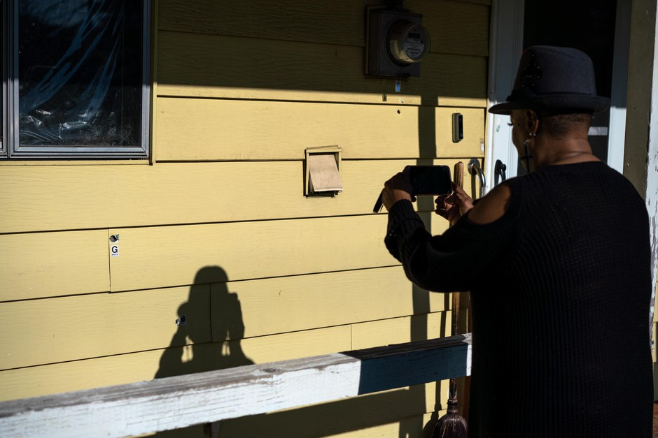 Antoinette Edwards takes a photo of bullet holes in an elderly couple's North Portland home on Jan. 30, 2019, in North Portland, Ore.