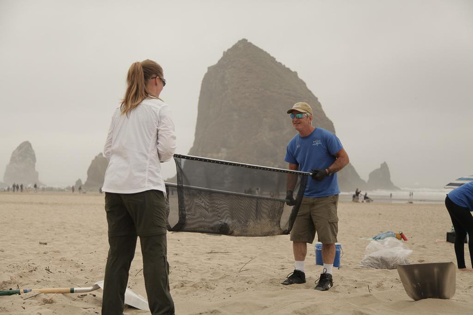Valerie Schockelt (left) and Marc Ward use a microplastics filtration device to filter sand at Cannon Beach with iconic Haystack Rock in the background.