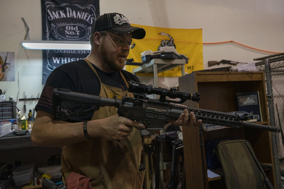 Jon Bush, a gunsmith in Vancouver, WA, holds his AR-15 in his shop. Bush says the AR-15's popularity has largely to do with the rifle's appearance.