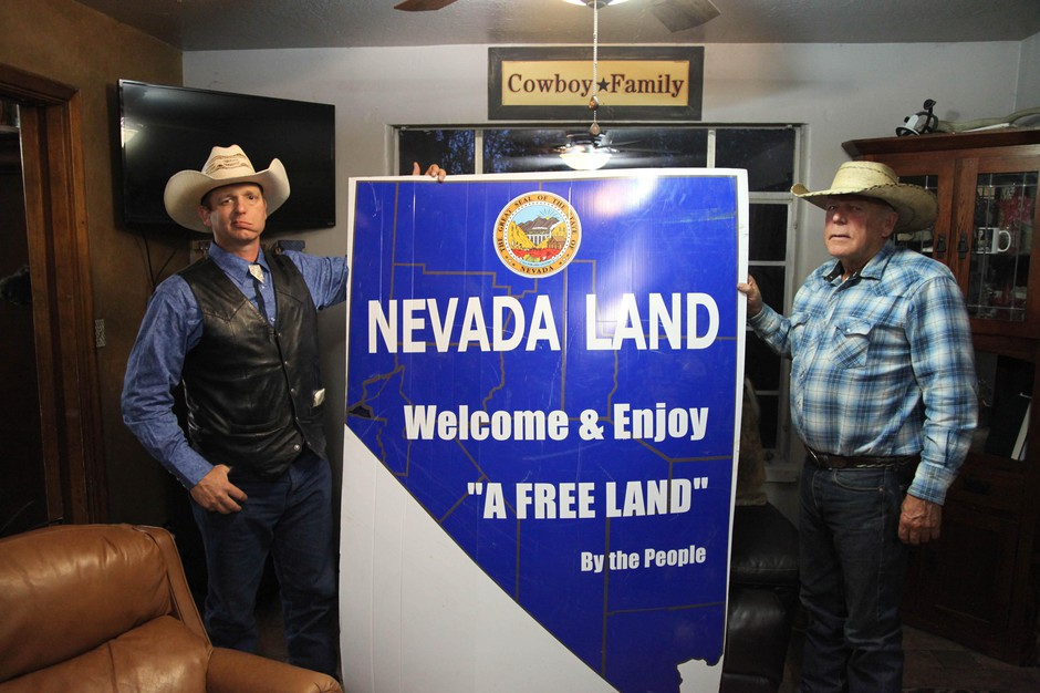 Ryan Bundy, left, and Cliven Bundy hold up a sign in their living room. Ryan Bundy is running for governor as a next step in the family's fight to remove the federal government from Nevada.