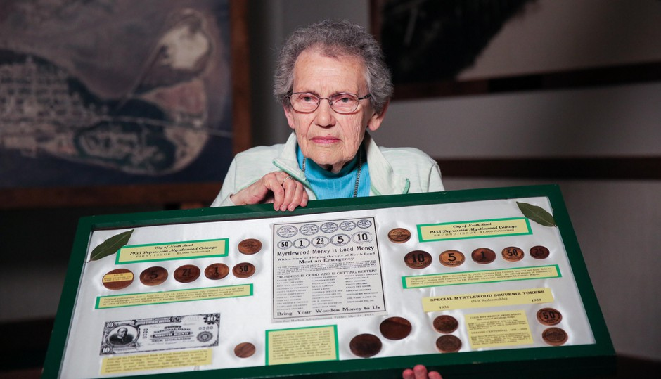 Lifelong North Bend, Oregon, resident Pat Choat Pierce poses with her collection of the city's myrtlewood money. Pierce is widely regarded as the foremost expert on North Bend's wooden currency.