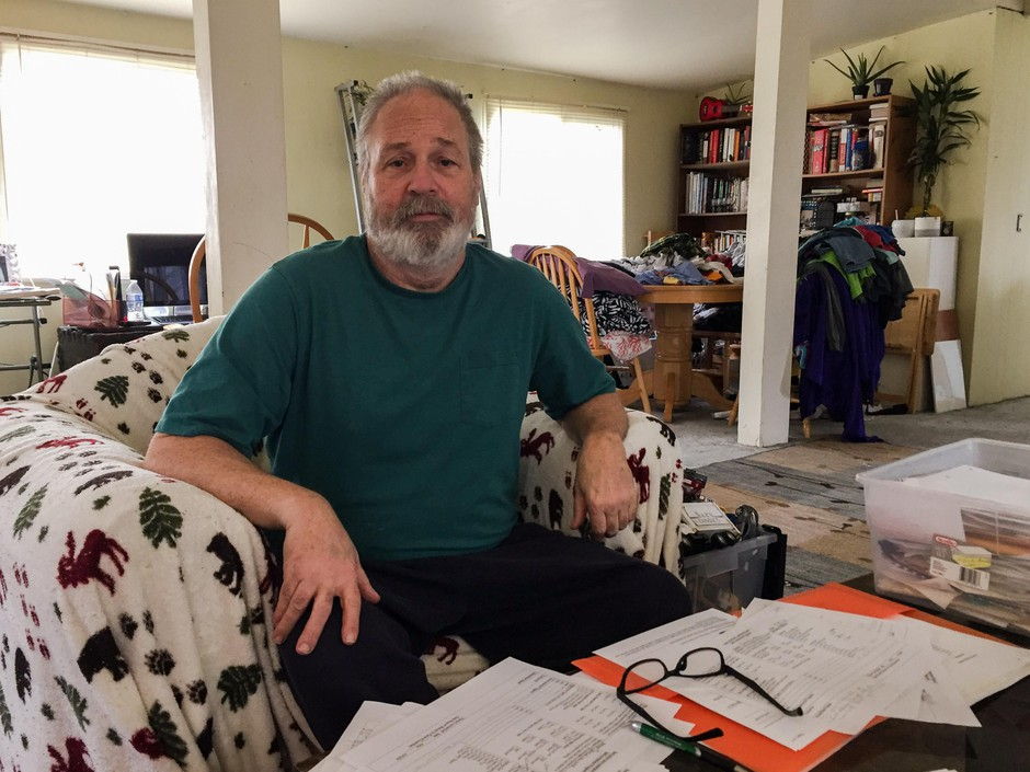 Nick Vervair sits on his couch looking over school records for his son. His boy was put in isolation at school on 17 different days in the 2014-15 school year, without the family knowing.