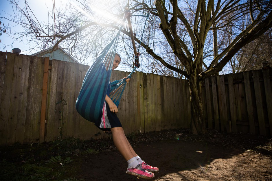 Jennifer, 12, swings from a tree in the backyard of her family's home in Hillsboro, Ore., Friday, March 1, 2019.