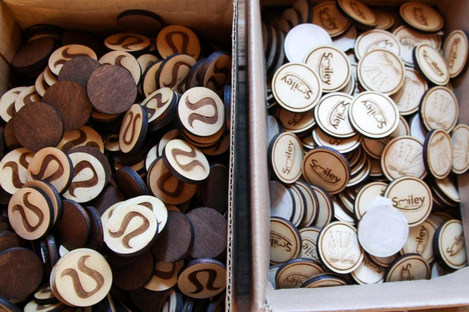 An example of the laser-engraved wooden tokens Toasted Maple makes for clients like Lululemon from its workspace in The Dalles, Ore., July 18, 2019. Owner Lindsey Brady is paying for software to stay compliant on other states' sales tax rules.
