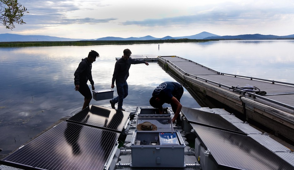 Mohammed Bawazeer (left) and Ian Riley carry a battery that will power the lake aeration system for 32 hours, even if the sun isn't shining.