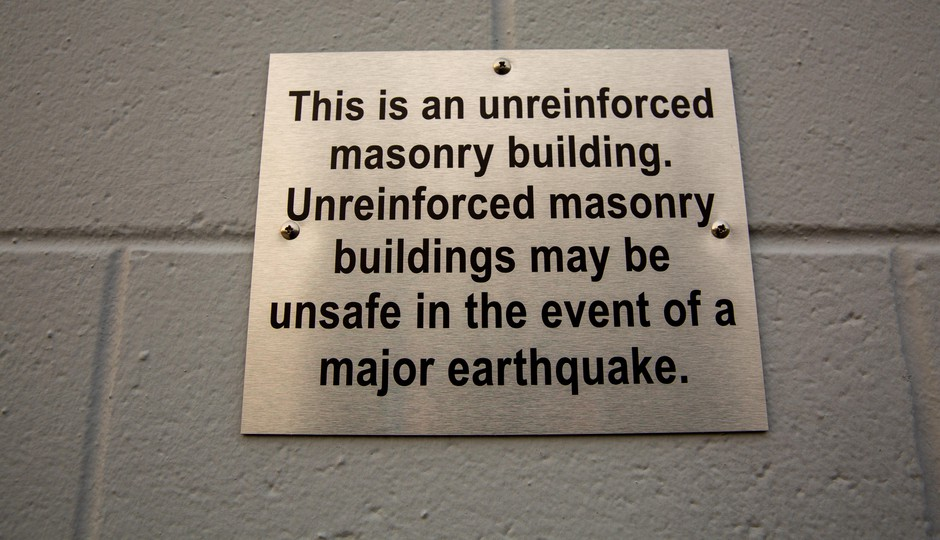 A sign on a business in Northeast Portland warns visitors that the building is constructed of unreinforced masonry on Tuesday, Oct. 22, 2019.