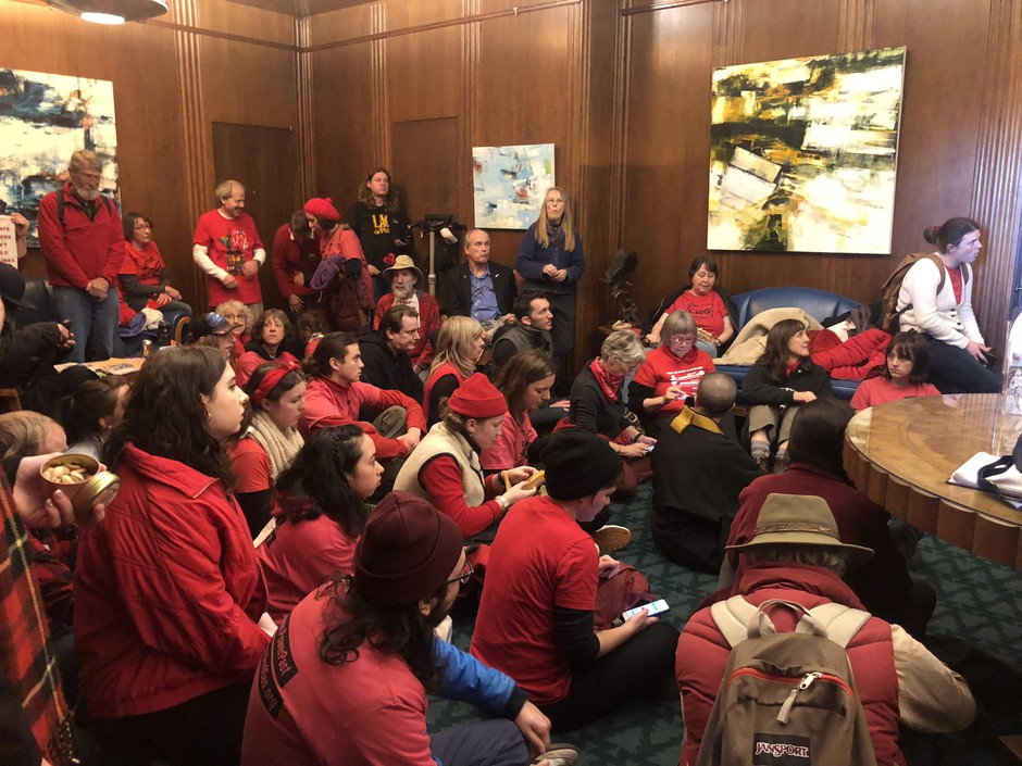 Activists with Oregon Rising Tide sit in at Gov. Kate Brown's office Thursday, Nov. 21, 2019, in Salem, Ore., demanding she come out against the Jordan Cove LNG project on the coast.