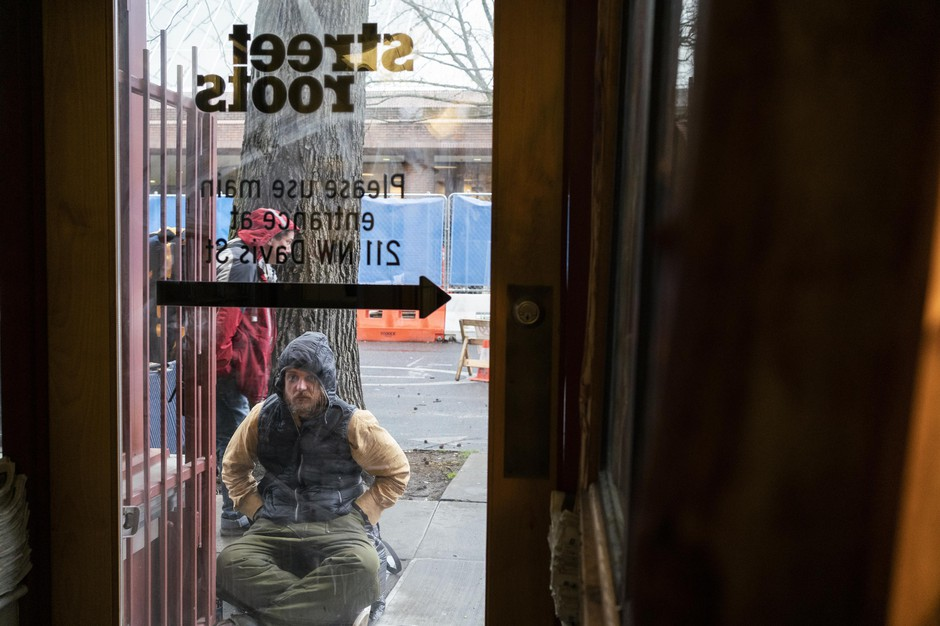 An unhoused person waits for Street Roots to open on March 25, 2020 in Portland, Oregon. The organizationis coordinatingan outreach program distributing hygiene supplies and coronavirus information to Portland's unhoused community.