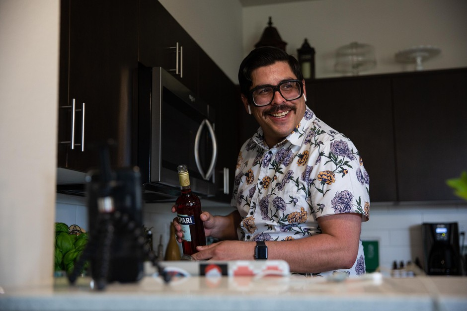 Bartender Joshua Madrid pours campari during his virtual happy hour Saturday, May 9, 2020, in Portland, Ore. Madrid started broadcasting drink-mixing lessons on his Facebook page when the COVID-19 pandemic forced closure of Oregon bars and restaurants.