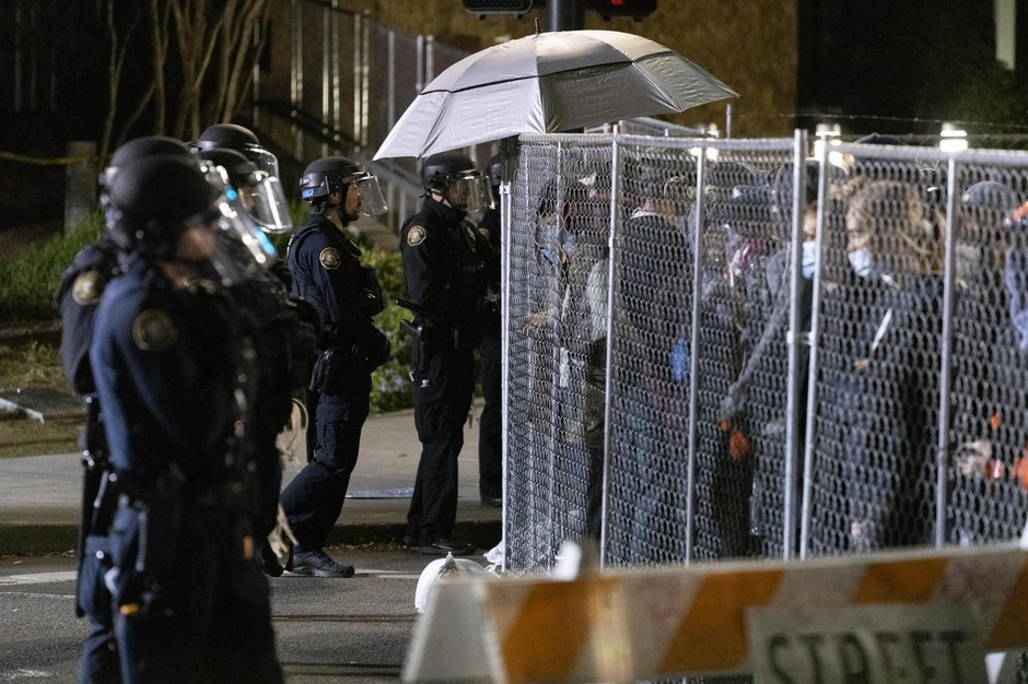 Police and protesters face one another through a chain link fence in downtown Portland the night of June 3, 2020.