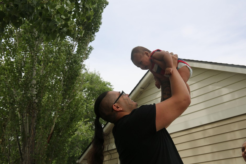 Dyami Ellis plays with infant son Brave Bear seven weeks after their entire household tested positive for COVID-19. Culver, Ore., June 24, 2020.