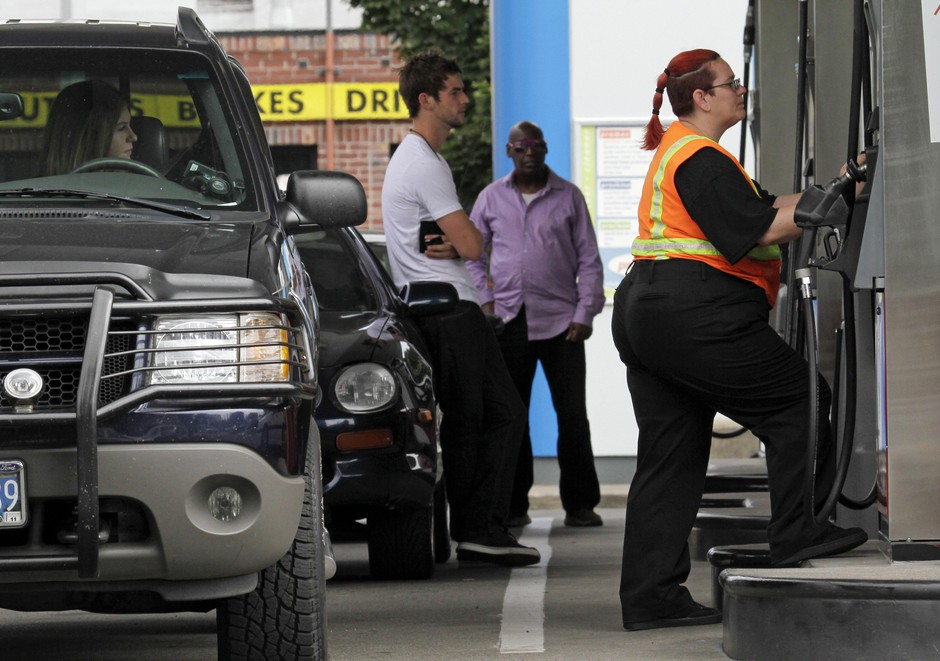 Customers stand in line as Jaqueline Henderson, right, prepares to pump gas at a station in Portland, Ore., Friday, July 29, 2011.