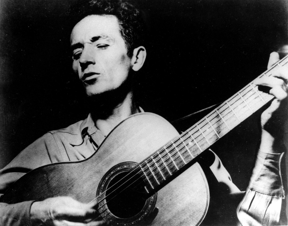 In this undated photo, folk singer Woody Guthrie plays his guitar.