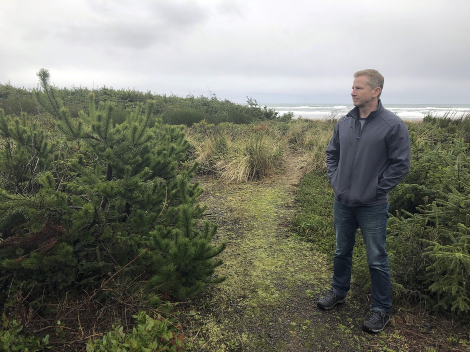 Jeff Bryner gazes, Wednesday, Jan. 8, 2020, at the lot that a Facebook subsidiary bought to convert it into a landing site for a trans-oceanic cable in Tierra Del Mar, Ore.