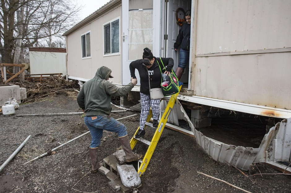 In this Feb., 8, 2020, photo resident Patty Haid is helped from her flood-damaged home in Pendleton, Ore. after returning to assess the damage from the flooding that struck last Thursday and Friday. More than 50 people were rescued by helicopter over the weekend from flooding that swamped northeast Oregon and destroyed homes.