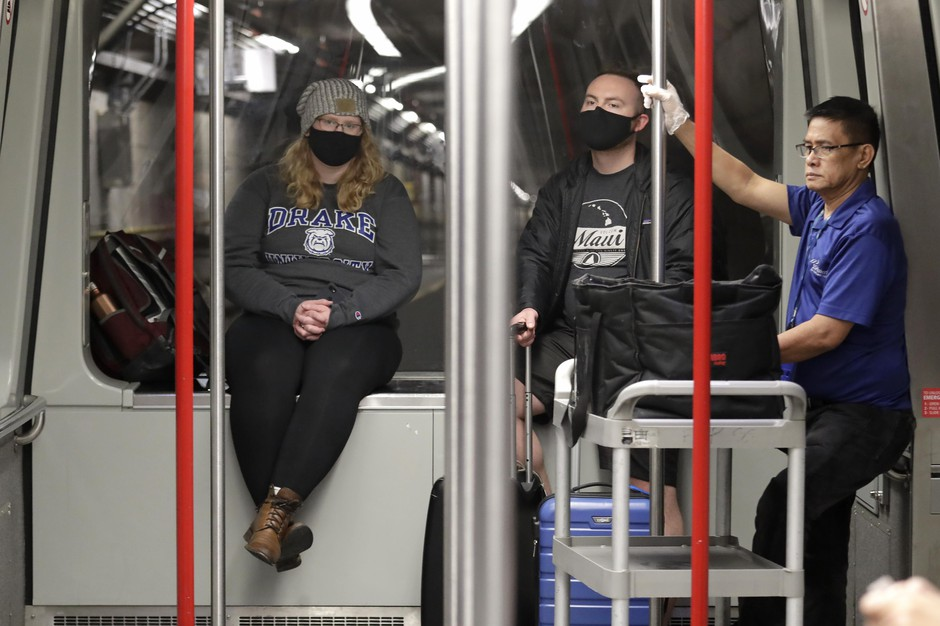 Travelers Meredith Ponder, left, and Coleby Hanisch, both of Des Moines, Iowa, wear masks to remind them not to touch their faces as they ride a train at Seattle-Tacoma International Airport Tuesday, March 3, 2020, in SeaTac, Wash.