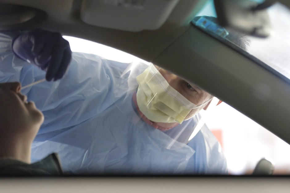A nurse at a drive-up coronavirus testing station set up by the University of Washington Medical Center uses a swab to take a sample from the nose of a person in a car Friday, March 13, 2020, in Seattle.