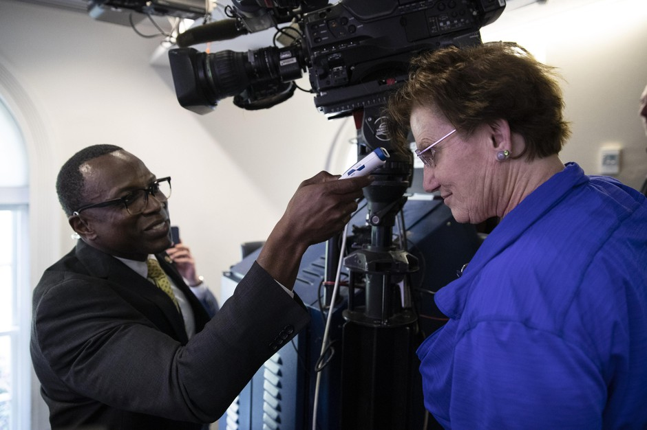 A member of the media, right, gets their temperature taken by member of the White House physicians office, over concerns about the coronavirus in the James Brady Briefing Room at the White House, Saturday, March 14, 2020, in Washington.