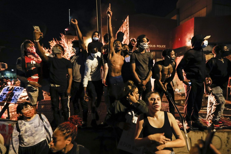 People demonstrate outside of a burning Minneapolis 3rd Police Precinct, Thursday, May 28, 2020, in Minneapolis.