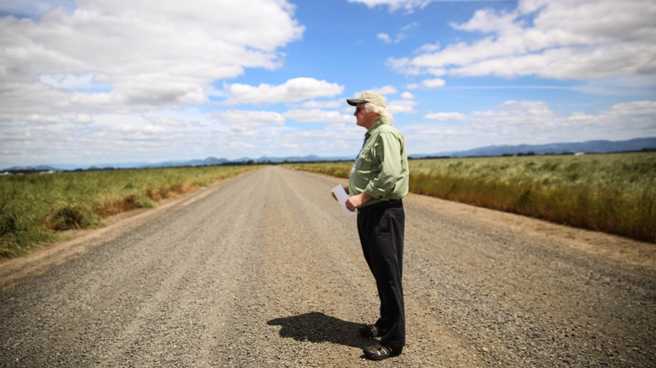 Cartographer Dave Imus stands in a country road.
