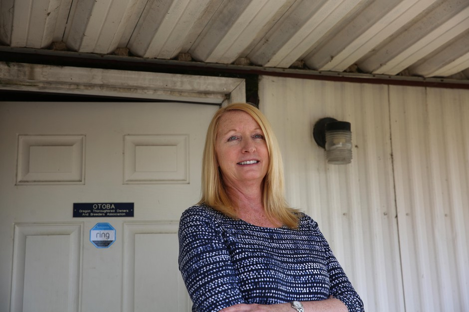 Lynelle Fox Smith outside the Oregon Thoroughbred Owners and Breeders Association on the back lot of Portland Meadows.