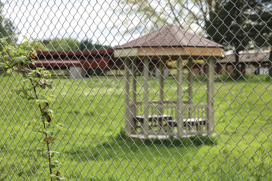 One of two small gazebos built on the Chemawa campus sits behind a fence.