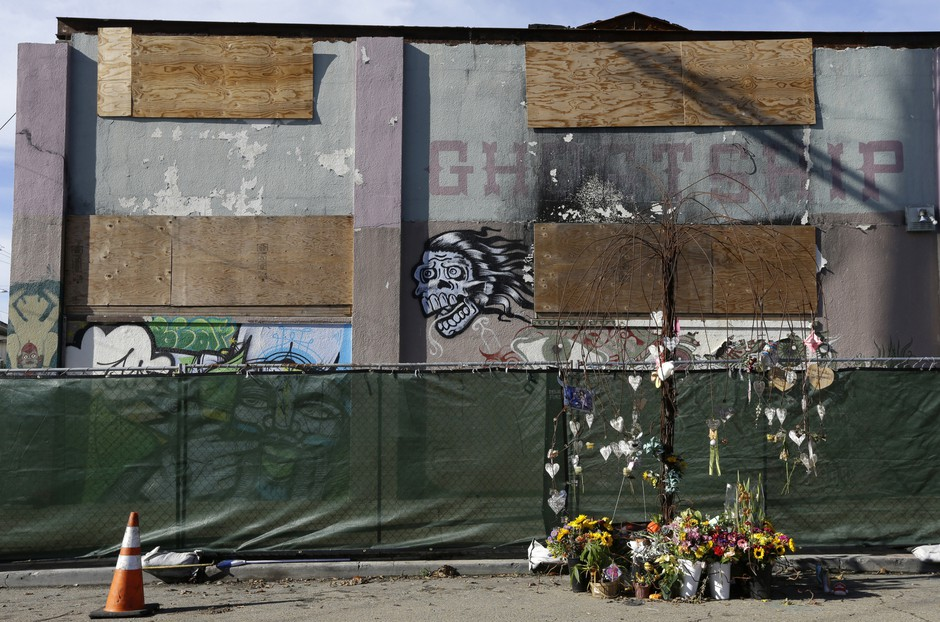 Flowers are left at a makeshift memorial to those who died outside an art collective known as the Ghost Ship warehouse in Oakland, Calif.