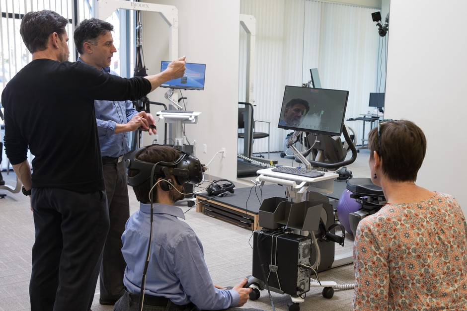 Firsthand Technology CEO Howard Rose (second left) lead a VR for pain management demo at Providence Gresham Rehab and Sports Therapy clinic.