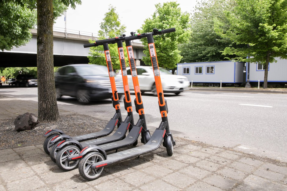 Commuters pass by a row of parked SPIN electric scooters on SW Naito Parkway in downtown Portland, Ore., on Friday, May 17, 2019.
