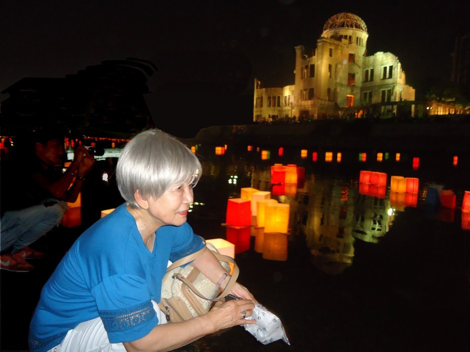 Dr. Hideko Tamura Snider lights a peace lantern in Hiroshima on the 70th anniversary of the Hiroshima bombing.
