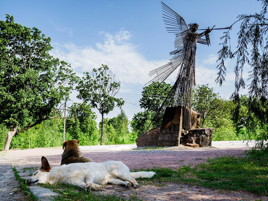 """Mia, lounging in front of the trumpeting angel memorial"", a film still from Julia Oldham's documentary, ""Fallout Dogs"", shot in the Chernobyl exclusion zone."