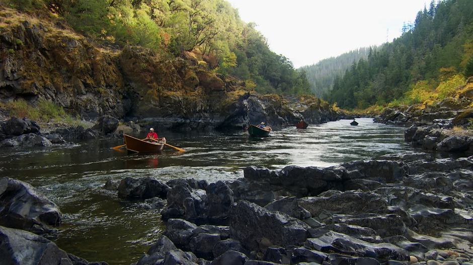 Hand-built wooden boats drift on the Wild and Scenic Rogue River.