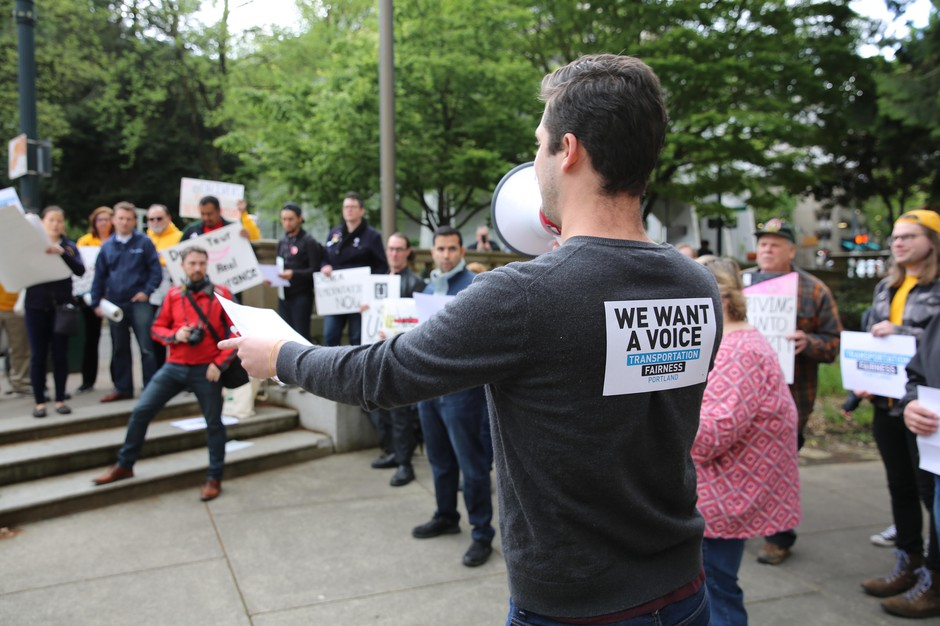 Full-time PSU student Owen Christofferson rallies a crowd of ride-hailing drivers outside Portland City Hall.